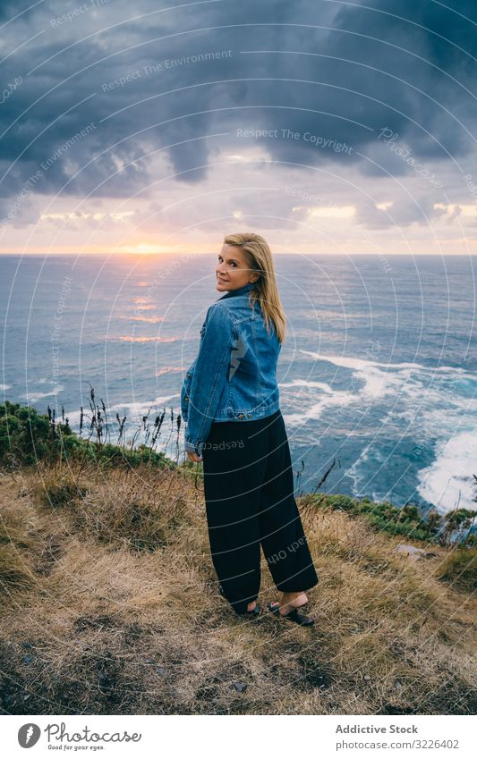 Woman on seashore against dusky clouds woman horizon seascape sunset harmony contemplation overcast chill scenic trip travel ocean tranquil recreation twilight