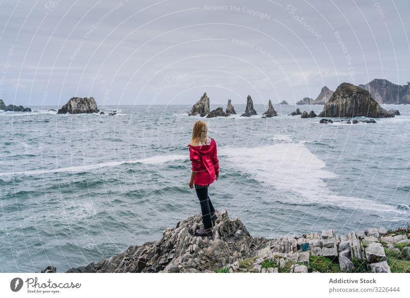Woman on stony seashore looking on foamy water washing peaks woman watching vacation tourism holiday relaxing adventure traditional destination ocean coastline