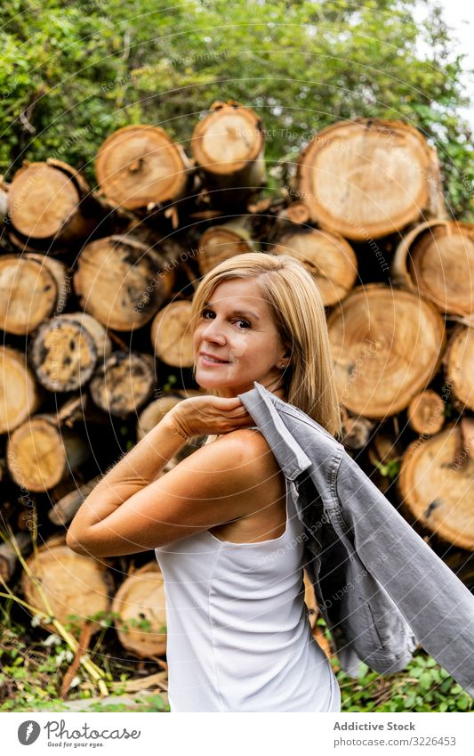 Woman taking off jacket on background of woodpile in forest log walking trunk woman firewood face model nature holiday smiling vacation weather lady journey
