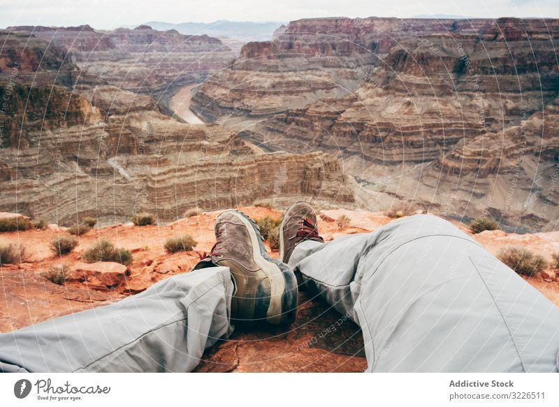 Exhausted male having break on deserted rock man canyon cliff tired exhausted recreate edge scenic usa nature hiker vacation rest relax travel landscape walk