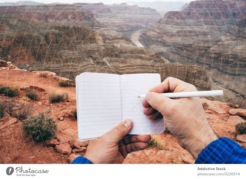Male drawing in notebook at rock man canyon cliff edge diary rest male usa nature travel landscape hiker terrain tourist grand park adventure national extreme