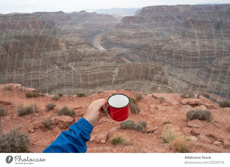 Male with cup of brew at rock man canyon cliff edge beverage relish break male usa nature travel landscape hiker terrain tourist grand park adventure national