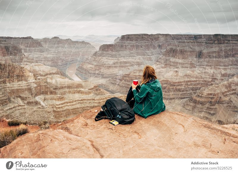 Female relaxing on cliff and admiring picturesque view woman canyon rest rock admire female tranquil jacket usa nature lifestyle hiking active sportswear sit