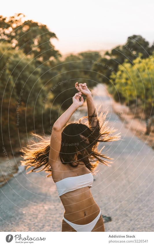 Woman in underwear and sneakers squatting on rural road woman nature tender lingerie slender countryside hide scared body white sunset natural gentle kneeling