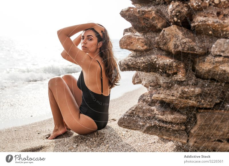 Pretty female in swimsuit sitting on sandy beach woman vacation sea fashionable stylish holidays destination recreation serious pensive concentrated pretty