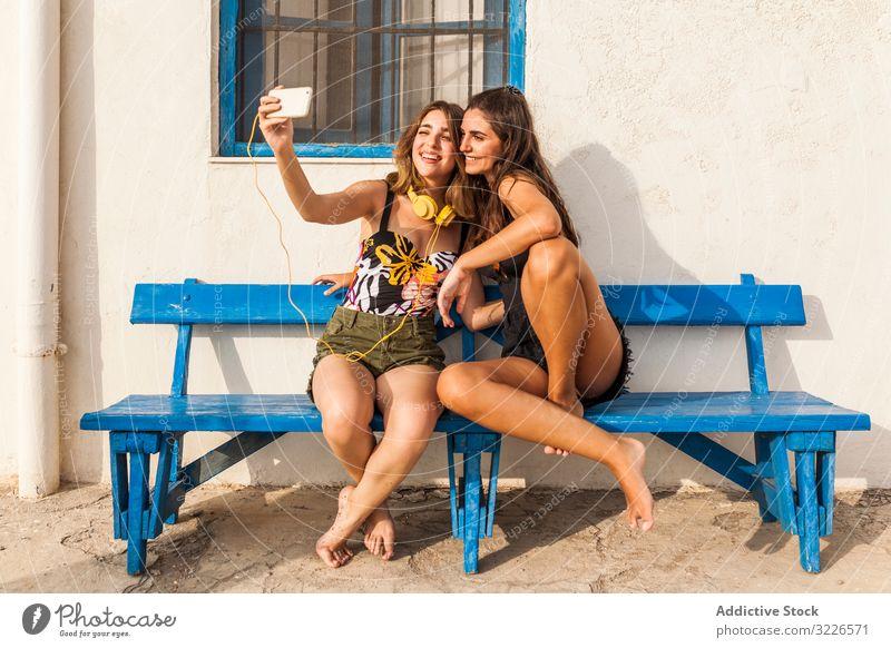 Girlfriends sitting on bench women love girlfriend affection best friend together smartphone alternative closeness lgbt lesbian teenager couple female brunette