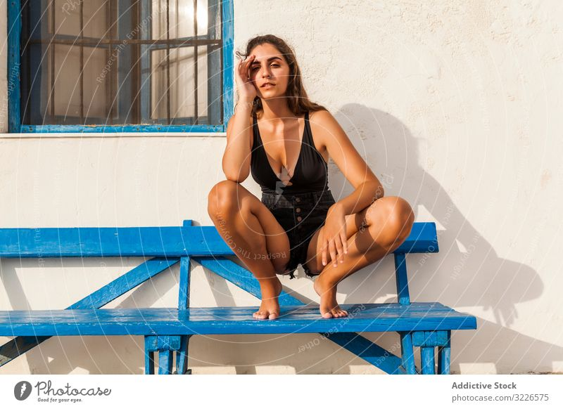 Young female relaxing on blue bench woman squat rest pensive recreation stylish casual pretty brunette slim trendy sad upset black shorts top barefoot tattooed