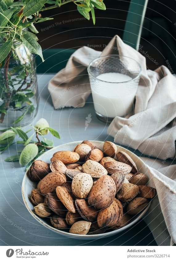 Glass of almond milk next to plate of almonds in shells on kitchen table glass nuts bowl cloth twig green plant rustic snack breakfast ingredient vegetarian