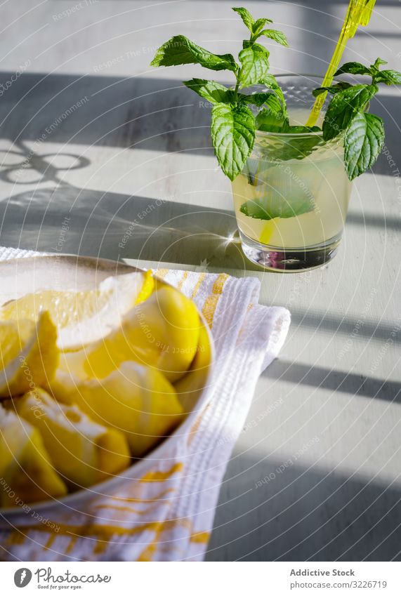 Glass of fresh lemonade next to plate with cut lemons on table glass piece juice kitchen wooden rustic homemade mint fruit drink food healthy natural citrus