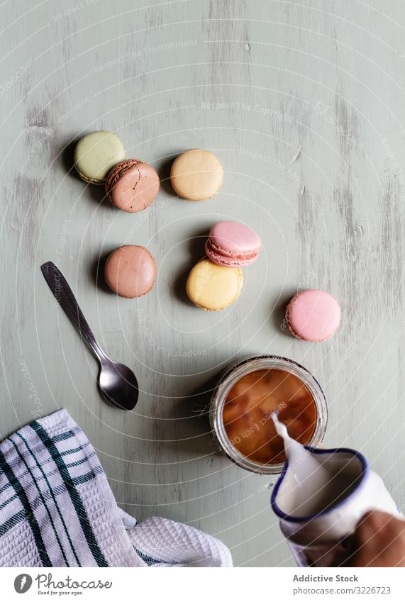Crop person adding milk to coffee near macaroons breakfast pour cup spoon napkin table food morning dairy meal dessert treat cookie biscuit tasty delicious