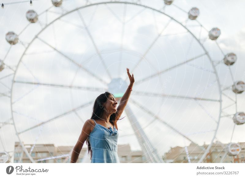 Dreamy woman resting by Ferris wheel in amusement park dreamy summer fairground sundress ferris wheel relaxed calm entertainment wistful long hair attractive