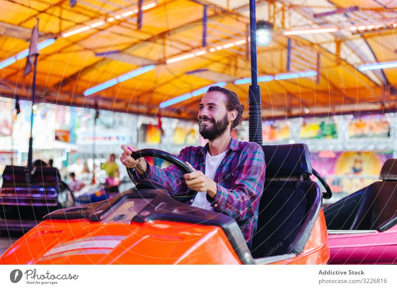 Happy hipster man riding electric car in amusement park ride joyful happy casual smile having fun attraction carnival fairground vibrant entertainment young