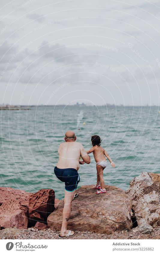 Grandfather and granddaughter having fun on rocky beach vacation grandfather ocean family elderly child girl water granddad nature shore enjoying retired