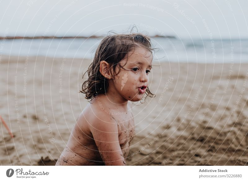 Inspired child playing with sand on beach summer vacation smeared digging holiday fun mouth girl game enjoyment expression activity cheerful joyful small