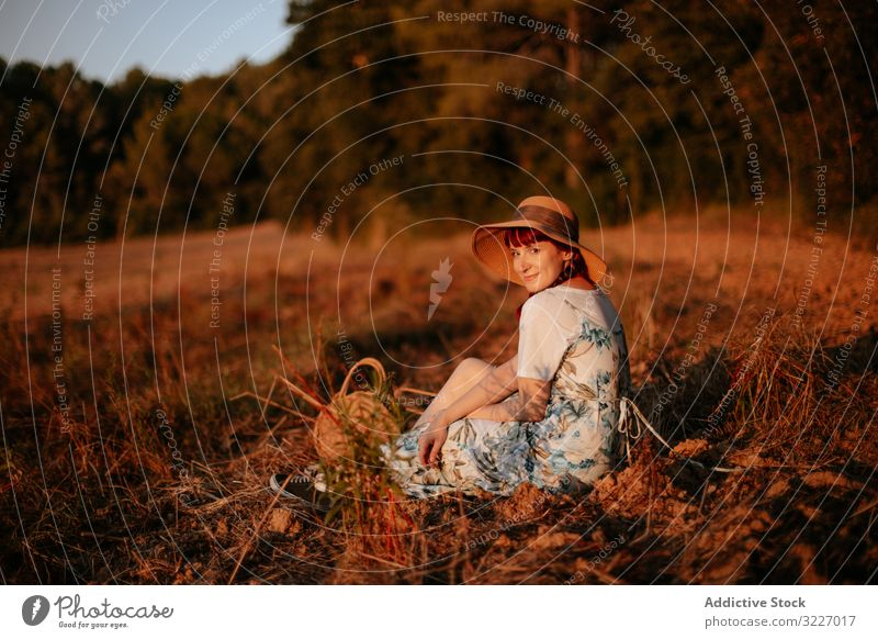 Woman sitting in field woman sunset retro nature evening sky countryside lifestyle female summer meadow vintage dress hat harmony idyllic calm tranquil serene