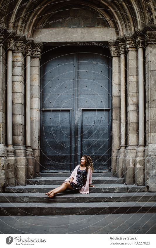 Lady resting near metal door on street tourist building woman old sit steps barcelona spain female relax lifestyle wanderlust traditional destination town