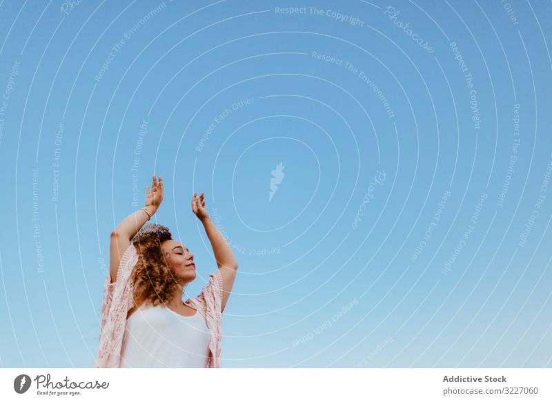 Happy woman raising arms to sky happy raised arms closed eyes nature freedom summer weekend peaceful female elegant vacation joy carefree calm tranquil serene