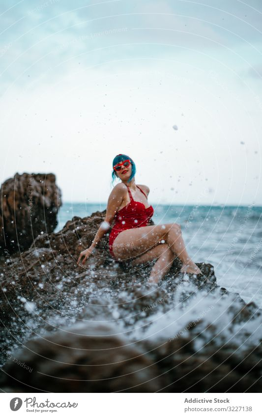 Graceful woman with trendy hairstyle tanning on rocky stone in water stylish sea shore retro relaxation fashion vintage elegant enjoyment swimwear classic lady