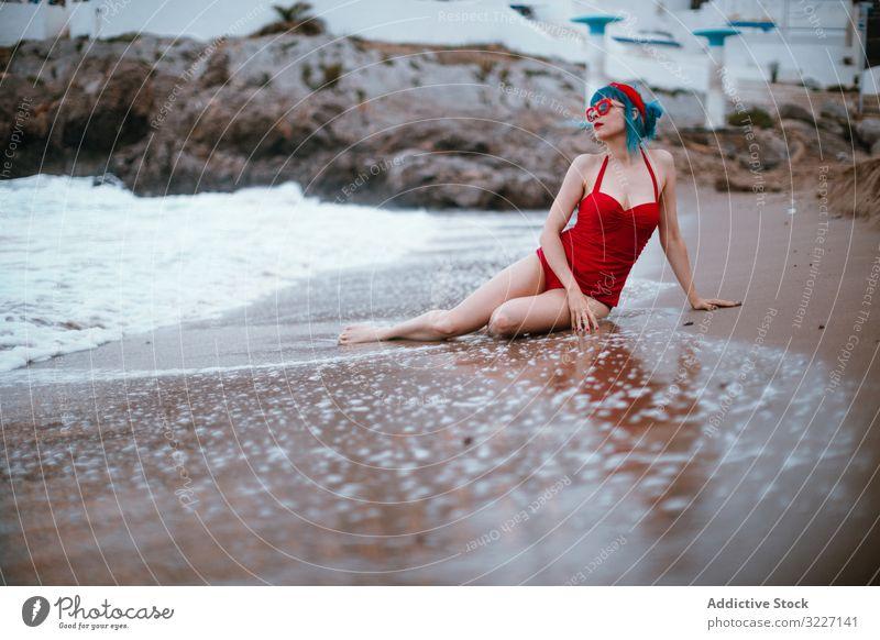 Relaxed woman in bright stylish swimsuit sitting on sandy beach sea retro adult sensual relaxation fashion vintage elegant enjoyment swimwear classic lady
