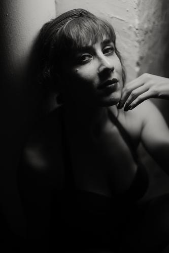 Dreamy woman in shadow touching face sensual shade touching chin human face brunette dark seduction temptation figure mysterious darkness bw tender