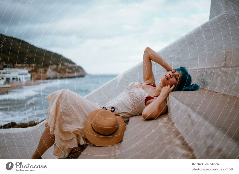 Sensual woman in sundress lying on pier stairs sensual step rest coast romantic allure staircase summer freedom seaside seafront beach hat colorful blue hair