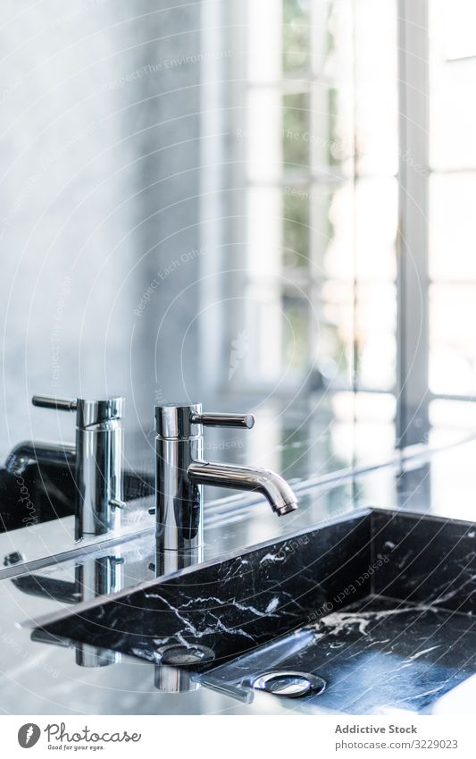 Marble sink and water tap in contemporary washroom bathroom marble washbasin faucet luxury metal detail mirror tile stainless tub rectangular steel hygiene