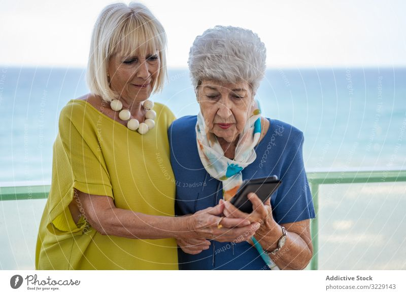 Senior ladies using smartphone on hotel balcony women elderly friend sea resort social media senior mature together friendship device gadget terrace elegant