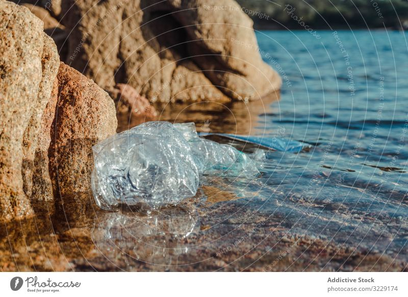 Plastic bottle lying on seashore plastic waste ecology nature beach pollution trash dirty harmful garbage litter rubbish sand marine hazard environment
