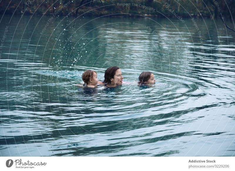 Mother with kids swimming in lake in spa mother family warm resort activity splash woman child sibling together leisure lifestyle relax rest vacation weekend