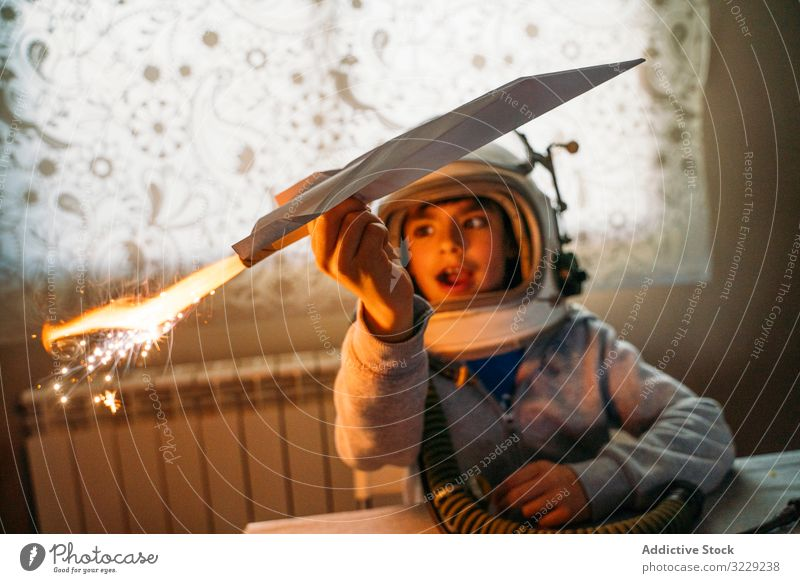 Dreamy kid having fun with toy airplane boy play fantasize paper dreamy astronaut helmet home child happy childhood leisure game joy cute cheerful sit rest