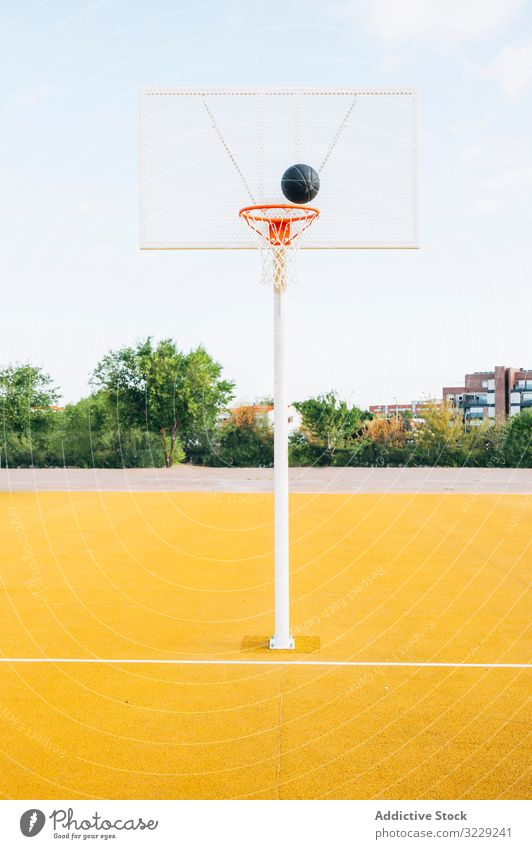 Outdoor yellow basketball court and black ball man athlete competition sports equipment adult recreation action portrait active activity asphalt athletic city