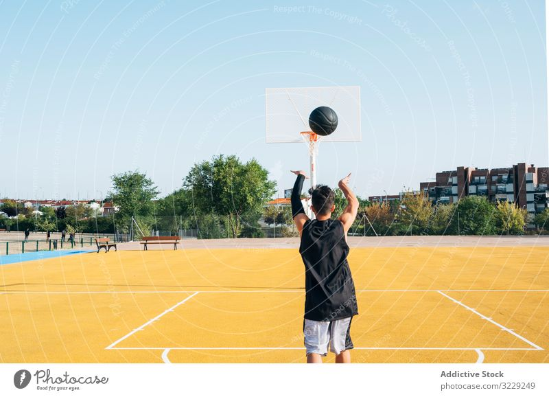 Young man playing on yellow basketball court outdoor. athlete competition sports equipment adult recreation action portrait active activity asphalt athletic