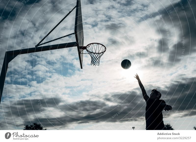 Young man playing on basketball court outdoor. athlete competition sports equipment adult recreation action portrait active activity asphalt city drop drops