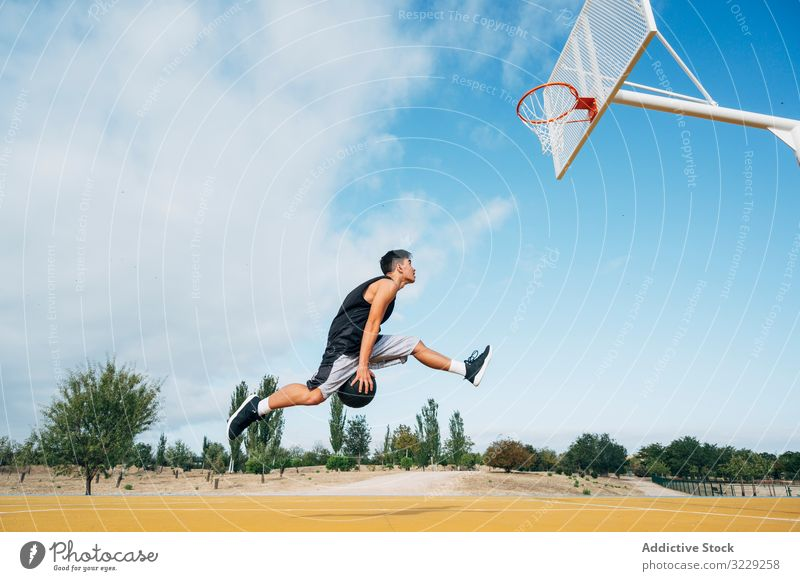 Young man playing on basketball court outdoor. athlete competition sports equipment adult recreation action portrait active activity asphalt athletic city drop