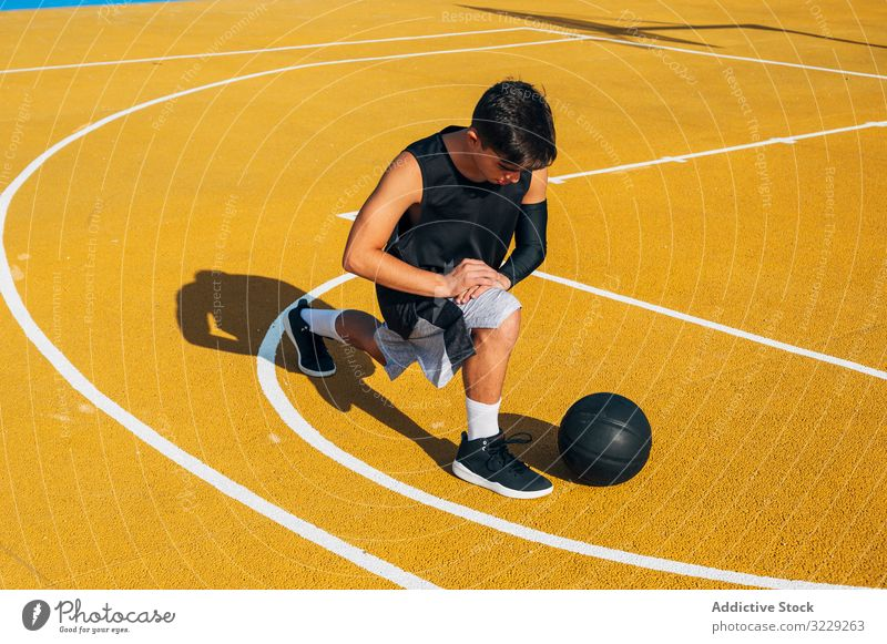 Young man and ball stretching on basketball court outdoor athlete competition sports equipment adult recreation action active activity asphalt athletic city