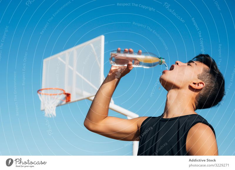 Young man playing on basketball court outdoor drinking water athlete competition sports equipment adult recreation action portrait active activity asphalt