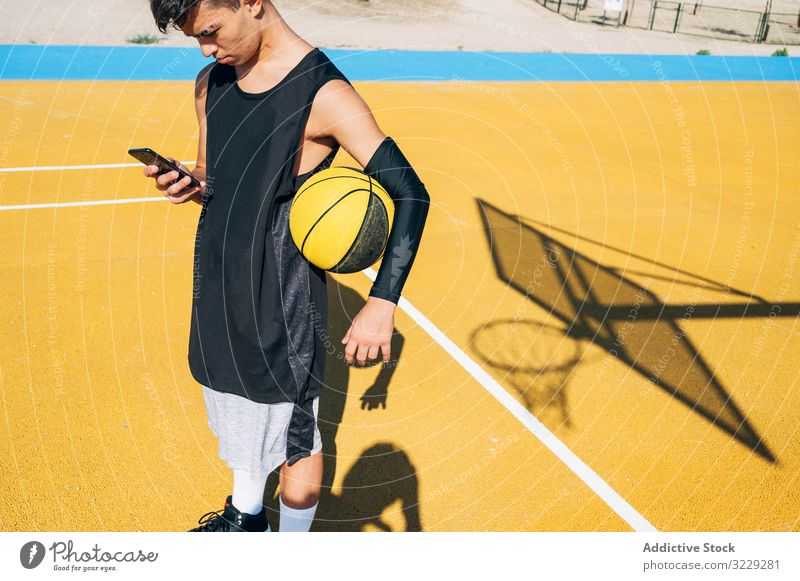 Male basketball player using his smartphone resting after training people outdoors man city sport street urban young activity yellow city life court daylight