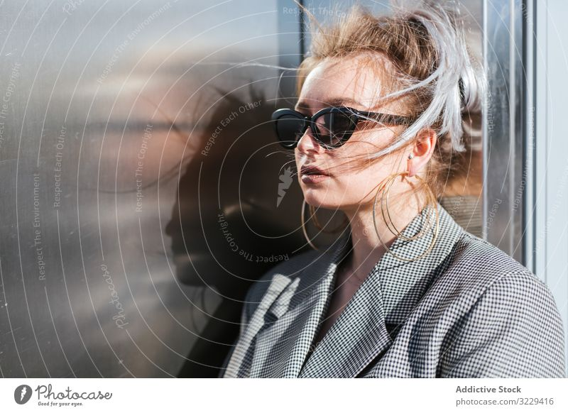 Stylish woman in black sunglasses leaning on metal wall fashion trendy model urban earring vintage grey plump retro street lady vogue jacket attractive stylish