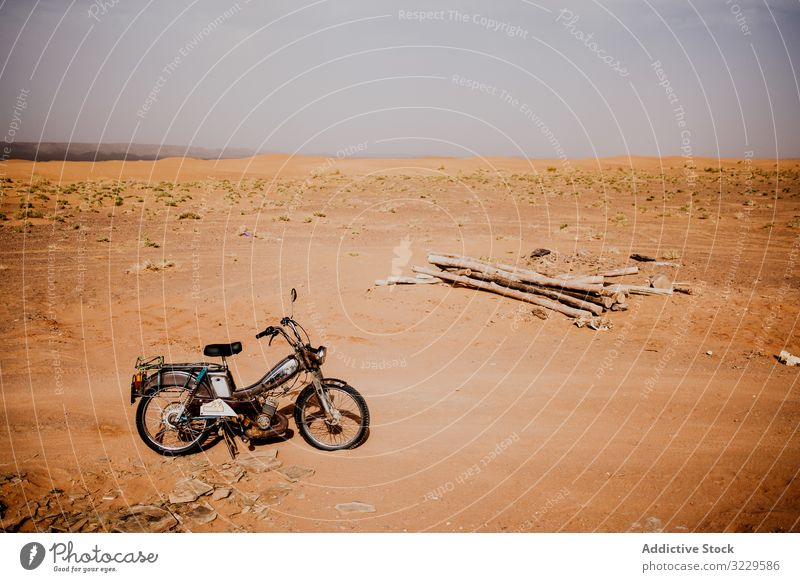Motorbike and logs in desert motorcycle travel sand wood pile morocco africa parked transport vehicle motorbike trip journey lumber arid dry drought sky nature