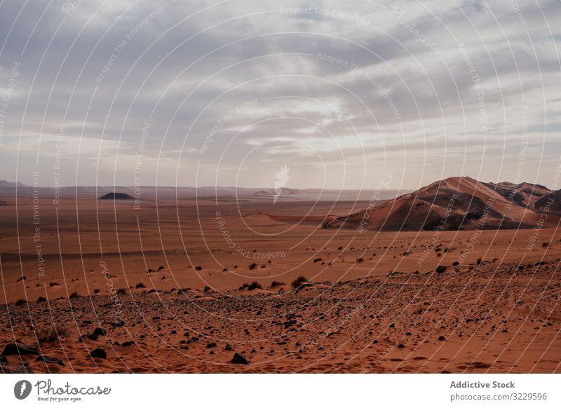 Sunset sky over hills in desert sunset sand cloudy rock arid morocco africa evening nobody landscape nature dune stone boulder sundown dusk twilight drought dry
