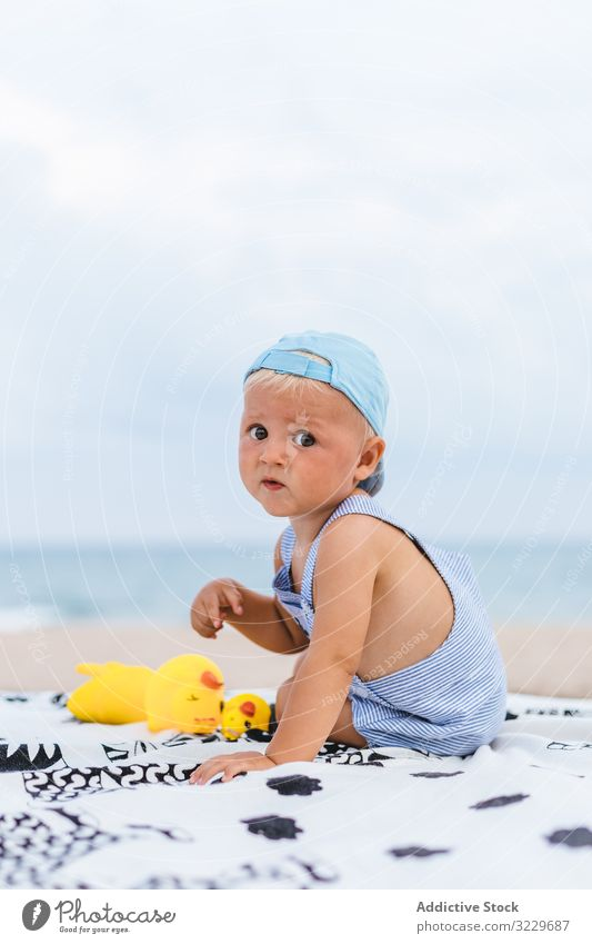 Rear view of a baby with a cap protection boy copy space holidays children kids toys morning caucasian happy back sea childhood people ocean outdoor person