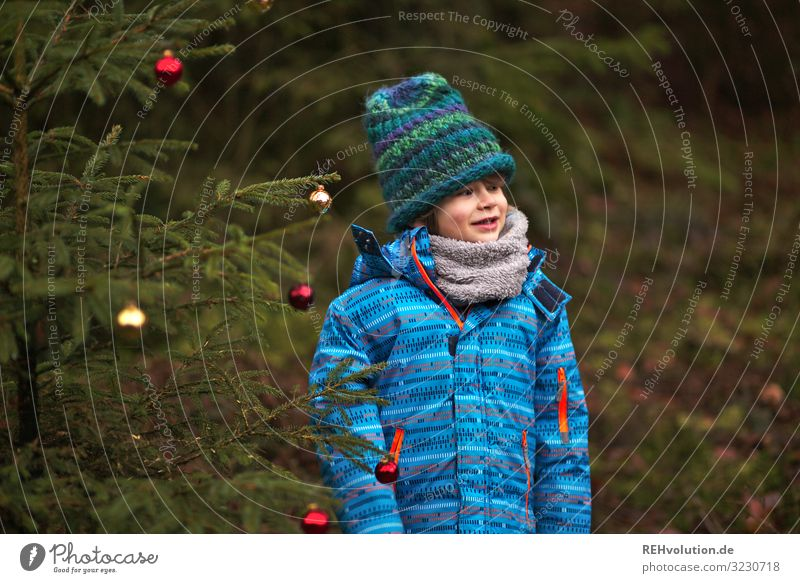 Child stands at a Christmas tree in the forest Front view Upper body portrait Central perspective Shallow depth of field blurriness Day Exterior shot