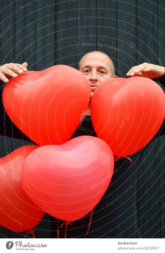 matter of the heart Feasts & Celebrations Man Adults 1 Human being Wall (barrier) Wall (building) Facade Decoration Balloon Heart Looking Stand Red Black