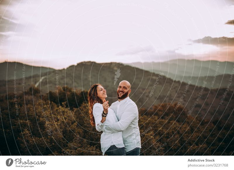 Affectionate couple having fun on hilly valley affectionate field nature happy mountain love smile hills countryside white shirt grass young adult together
