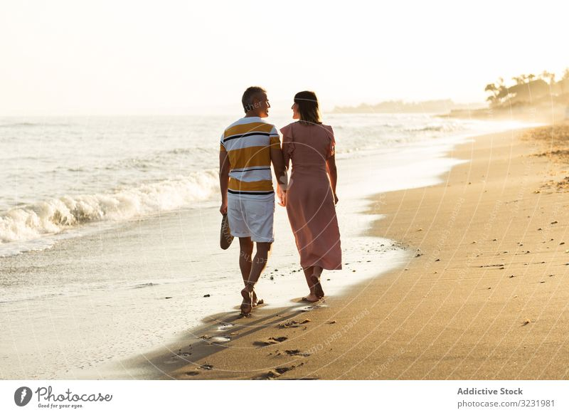 Adult couple walking towards sea beach sand wave resort together holding hands vacation man woman adult barefoot honeymoon weekend water ocean happy holiday