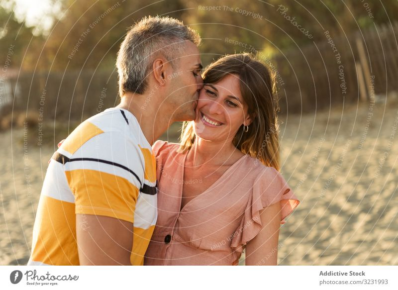Laughing couple hugging on sandy beach resort smile happy laugh fun love vacation sunny daytime man woman adult honeymoon summer nature shore coast relationship