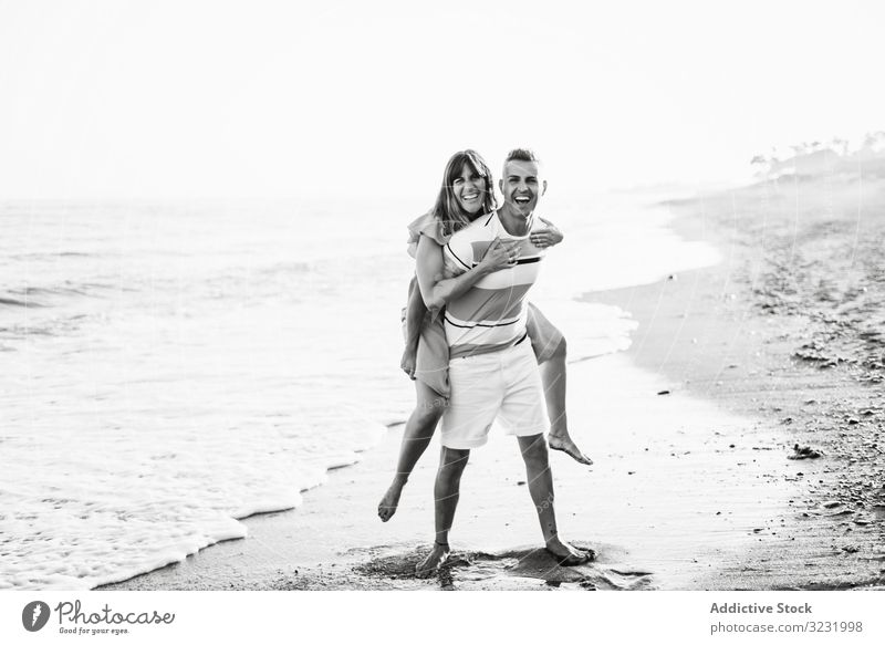 Man carrying woman on back near sea couple beach resort love piggyback ride smile happy vacation fun wave ocean water adult honeymoon summer shore coast