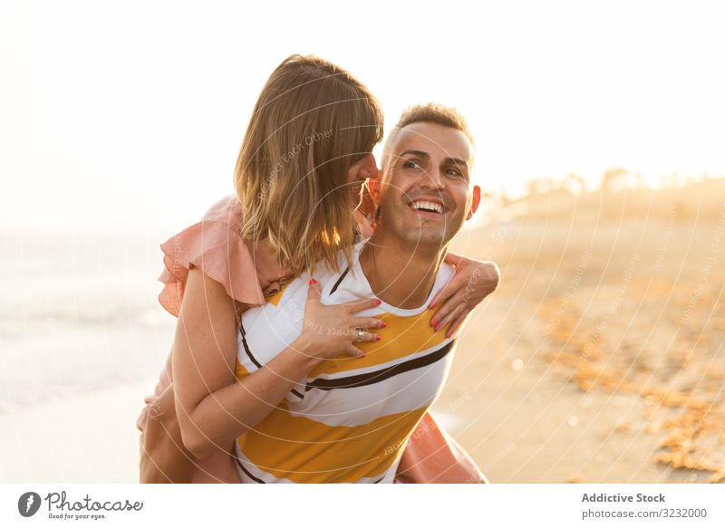 Man carrying woman on back near sea couple beach resort love piggyback ride smile happy vacation fun wave ocean water adult honeymoon summer shore coast