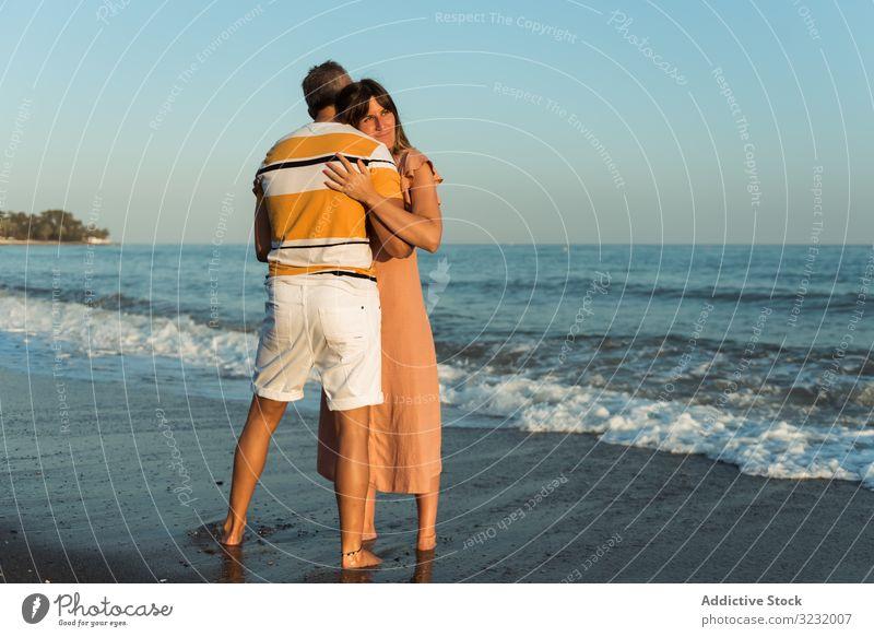 Adult couple embracing near sea beach resort love hug date smile happy vacation man woman adult honeymoon summer shore coast relationship water embrace ocean