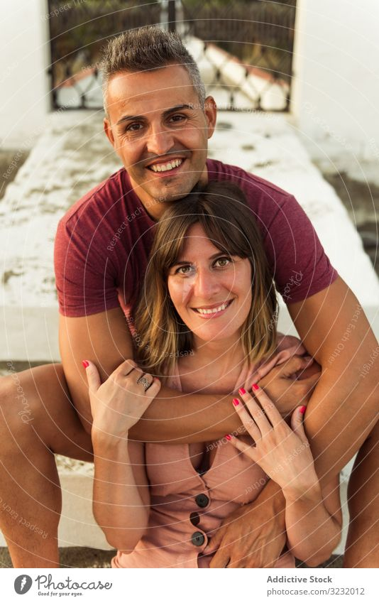 Adult couple hugging on steps love sit smile adult building relationship happy man woman together lifestyle leisure rest relax embrace stairs exterior romantic
